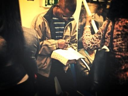 Leitor no Metrô de são Paulo lê a Bíblia, aqui, aberta no Livro dos Números.