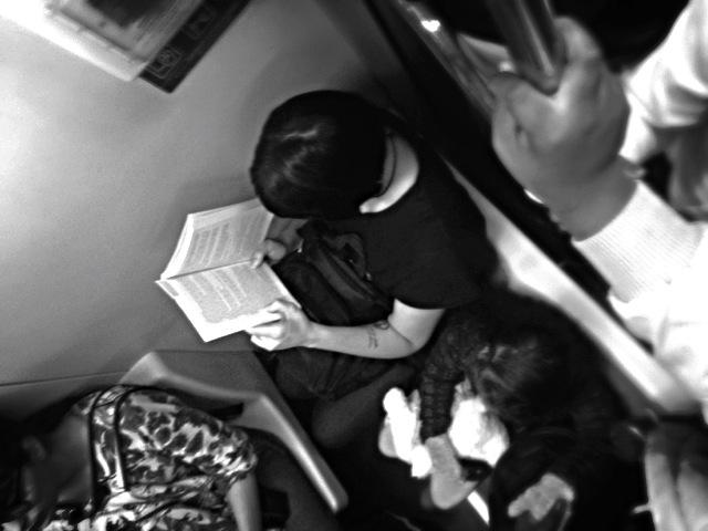 Sentada e compenetrada, leitora ostenta tatuagem no braço enquanto lê