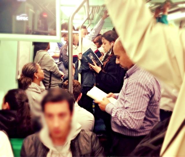 Leitora, em pé no meio do vagão, lê