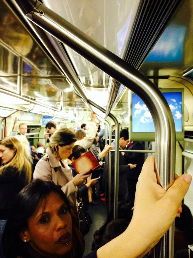 """Leitora de """"O Segredo"""", em dia de muito frio, no Metro de São Paulo."""
