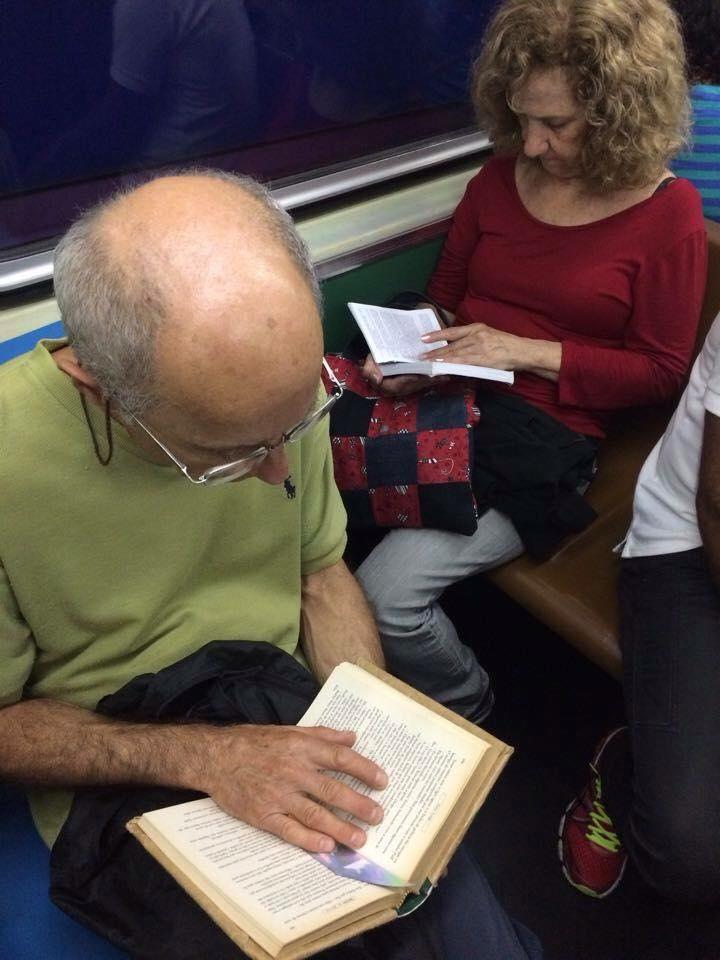"""A leitora, ao fundo, lê """"Lembranças que o Vento Traz"""", de Mônica de Castro; já o leitor, parece saborear um clássico da literatura universal"""